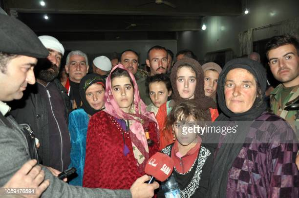 Handout picture released by the official Syrian Arab News Agency on November 9, 2018 shows a group of Druze women and children, abducted in July from...