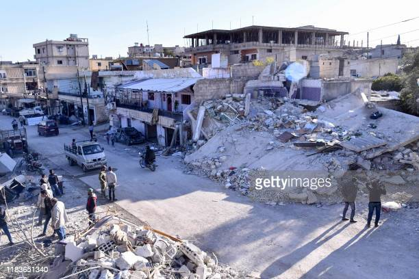 Handout picture released by the official Syrian Arab News Agency on November 20, 2019 shows people inspecting damaged buildings following a...