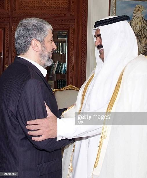 A handout picture released by the Qatari News Agency shows Qatari Emir Hamad bin Khalifa alThani welcoming Palestinian exiled Hamas leader Khaled...