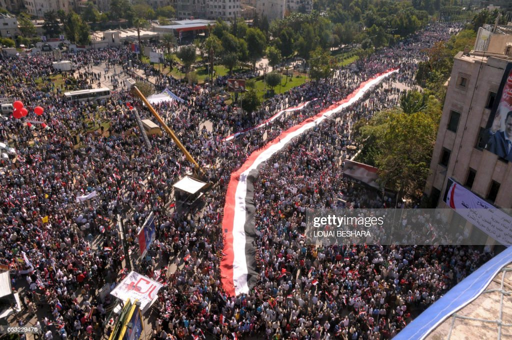 CREDIT 'AFP PHOTO / SANA' - NO A handout picture released by the Syrian Arab News Agency (SANA) shows hundreds of supporters of Syrian President Bashar al-Assad as they take part in a pro-regime rally in Aleppo, north of the capital Damascus on October 19, 2011. Assad's regime is facing international pressure amid a violent crackdown on anti-government protests that broke out in March across Syria. AFP PHOTO/HO-SANA / AFP PHOTO / SANA / Louai Beshara