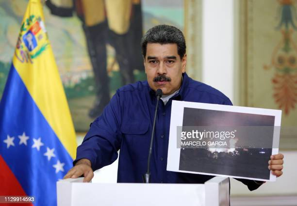 Handout picture released by the Venezuelan presidency showing Venezuelan President Nicolas Maduro showing a picture of the fire at a state owned...