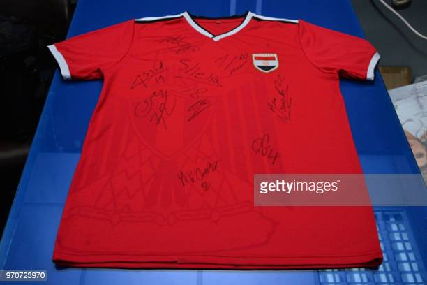 A handout picture released on June 10 by the Egyptian Civil Aviation Ministry shows a football jersey bearing the autographs of the members of...