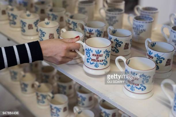 Handpainted commemorative mugs with a message celebrating the forthcoming wedding of Britain's Prince Harry and his US fiance Meghan Markle are...