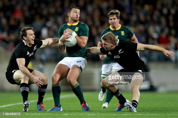 Handré Pollard of South Africa avoids the tackle of Ben Smith and Jack Goodhue of the All Blacks during the 2019 Rugby Championship Test Match...