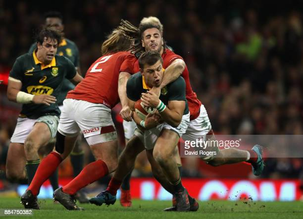 Handre Pollard of South Africa is tackled by Kristian Dacey and Josh Navidi during the rugby union international match between Wales and South Africa...