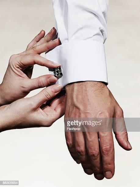 Hands adjusting cufflink