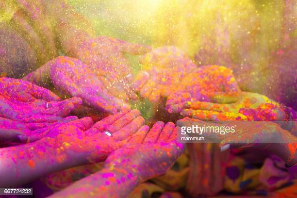 hands and colorful powders of the holi festival - holi stock pictures, royalty-free photos & images