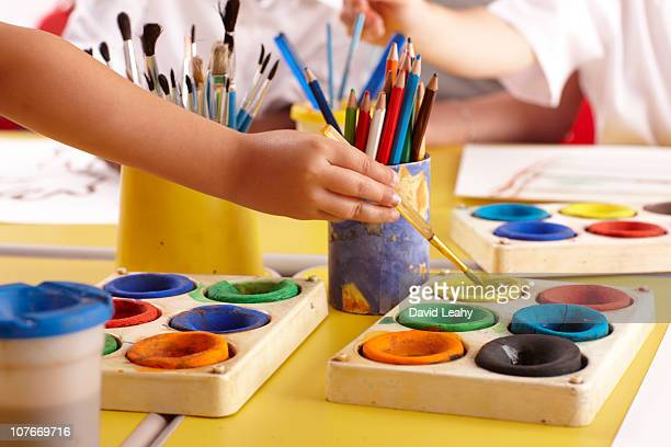 Hands and paints in classroom