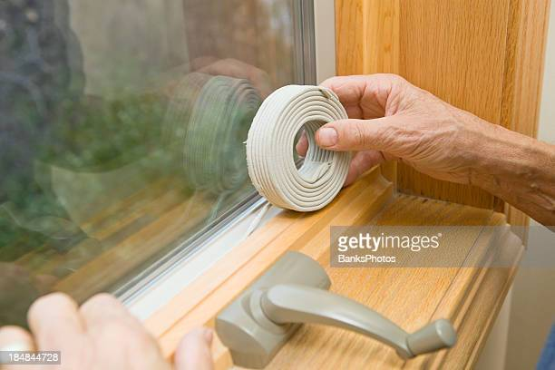 Hands Applying Weather Seal Caulk to Window Frame