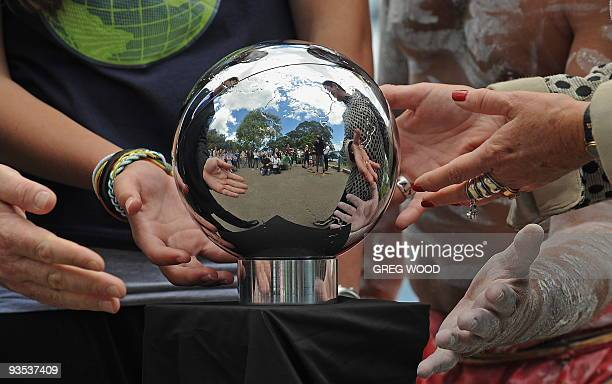 Hands are symbolically placed around 'The People's Orb' a shimmering 20cm silver sphere containing a 350 gigabyte mosaic of stories voices images and...
