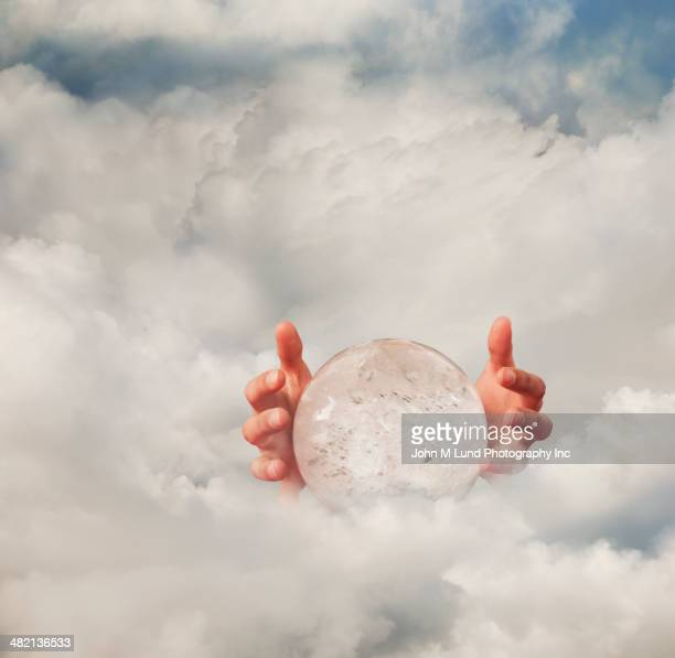 Hands around crystal ball in clouds