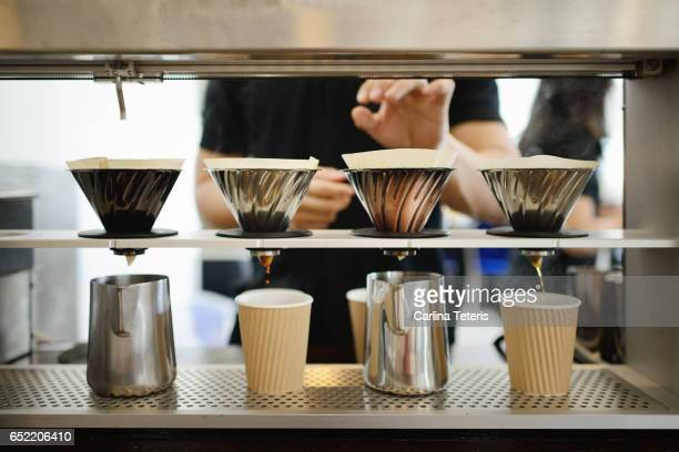 Hands at a coffee machine preparing four cups of drip coffee