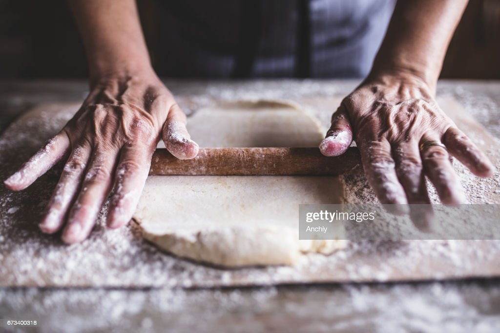 Hands baking dough with rolling pin on wooden table : Stock Photo