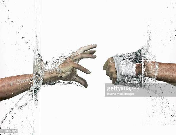 Hands breaking a  water wall