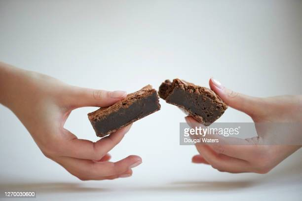 hands breaking chocolate brownie in half on white background. - cake stock pictures, royalty-free photos & images