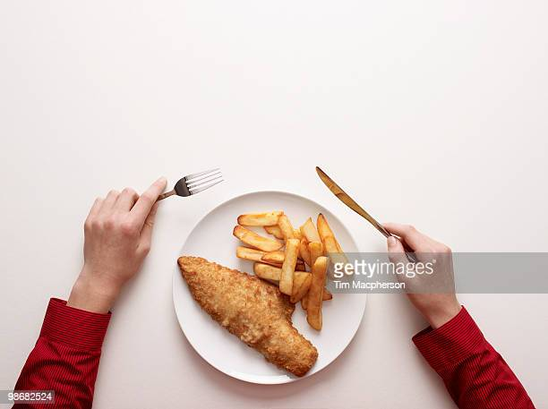 Hands by a plate of fish and chips