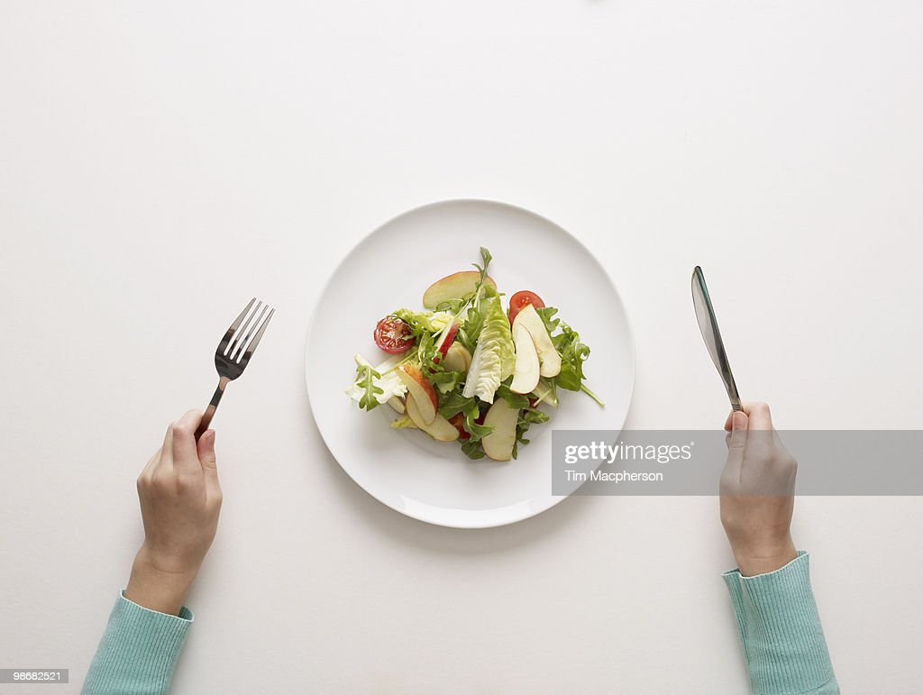 Hands by a plate of salad : Stockfoto