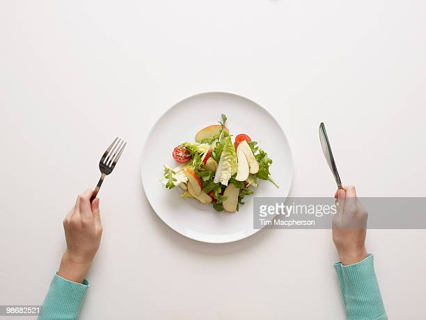 hands by a plate of salad - silverware stock pictures, royalty-free photos & images