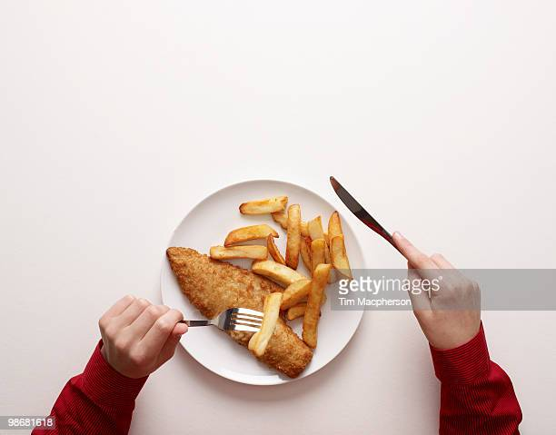 Hands by plate of fish and chips
