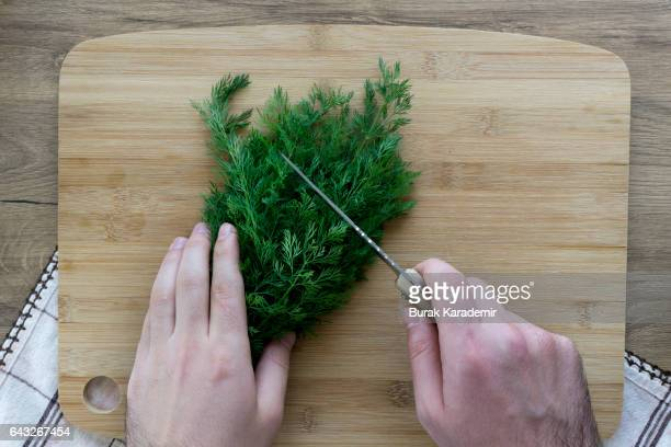 Hands chopping dill on wooden board.