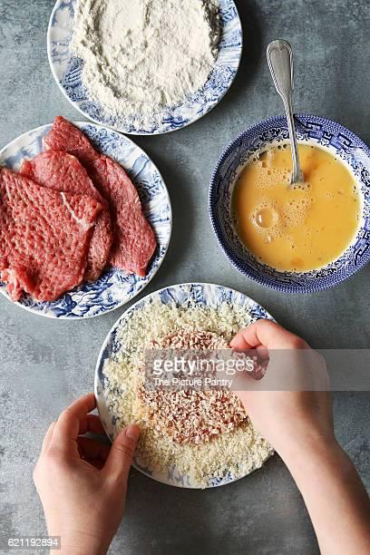 Hands coating beef in breadcrumbs. Preparing schnitzel