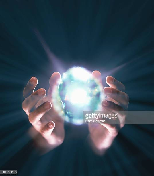 Hands coming around bright ball of light