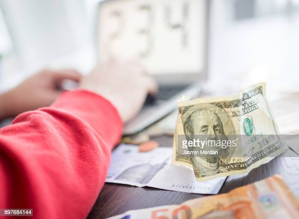 Hands counting different world currencies