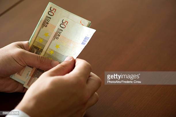 Hands counting fifty euro banknotes