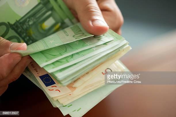 hands countong stack of money, cropped - euro stock-fotos und bilder