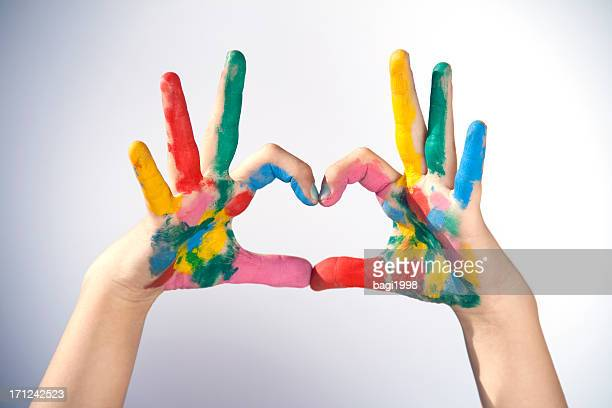 Hands covered in paint making a heart sign