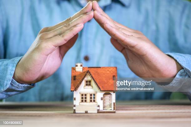 hands covering a toy house. home protection concept - home insurance stock pictures, royalty-free photos & images