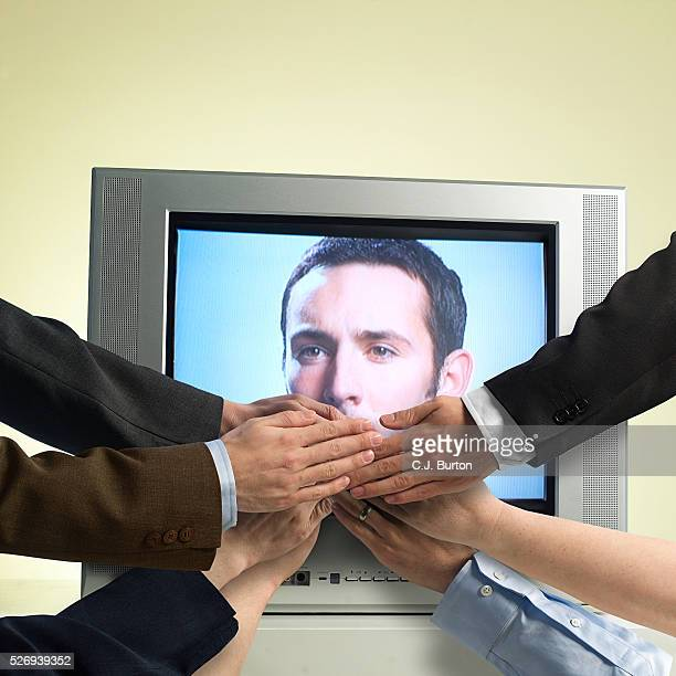 Hands covering mouth of man displayed on tv