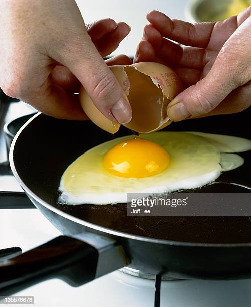 Hands cracking egg into frying pan