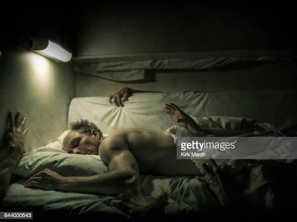 Hands crawling towards Caucasian man sleeping in bed