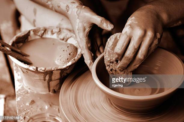 Hands creating a pottery bowl on a wheel