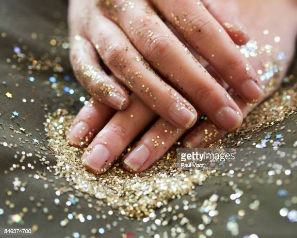 hands crossed covered in glitter