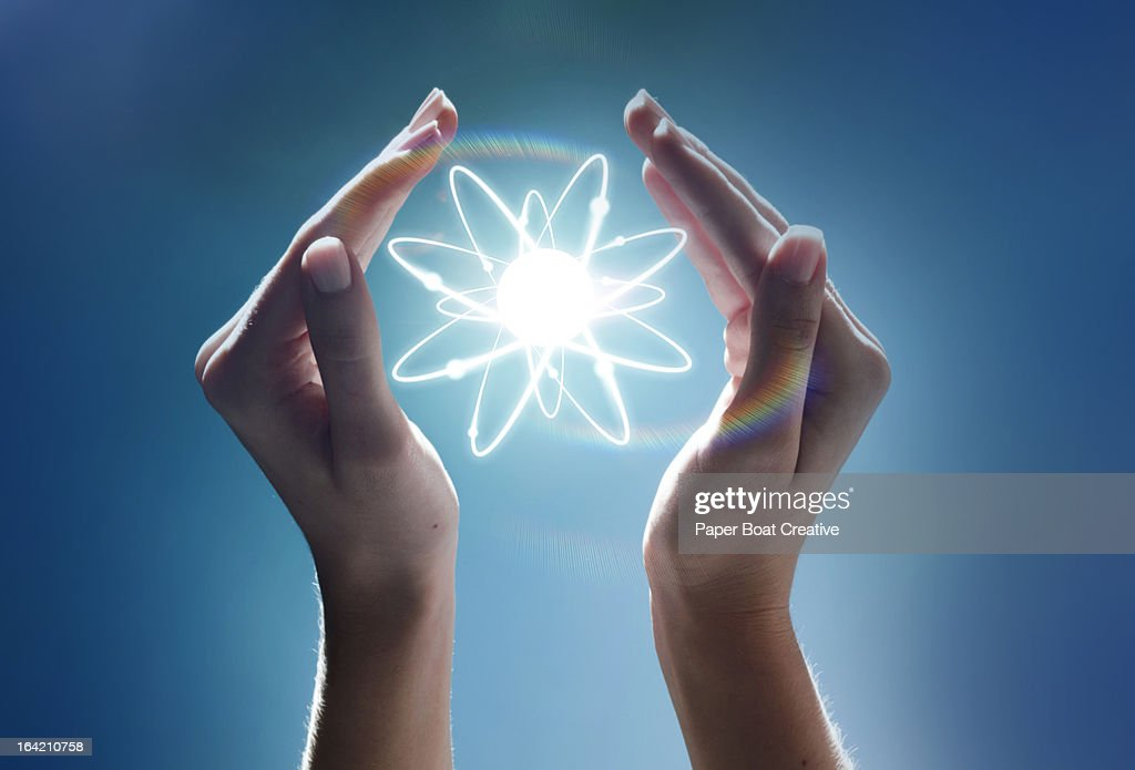 Hands cupping a glowing atom in the studio : Stock Photo