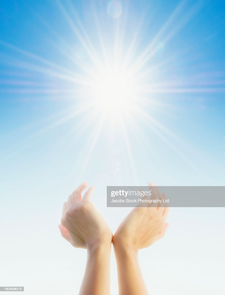 Hands cupping around sun in blue sky : Stock Photo