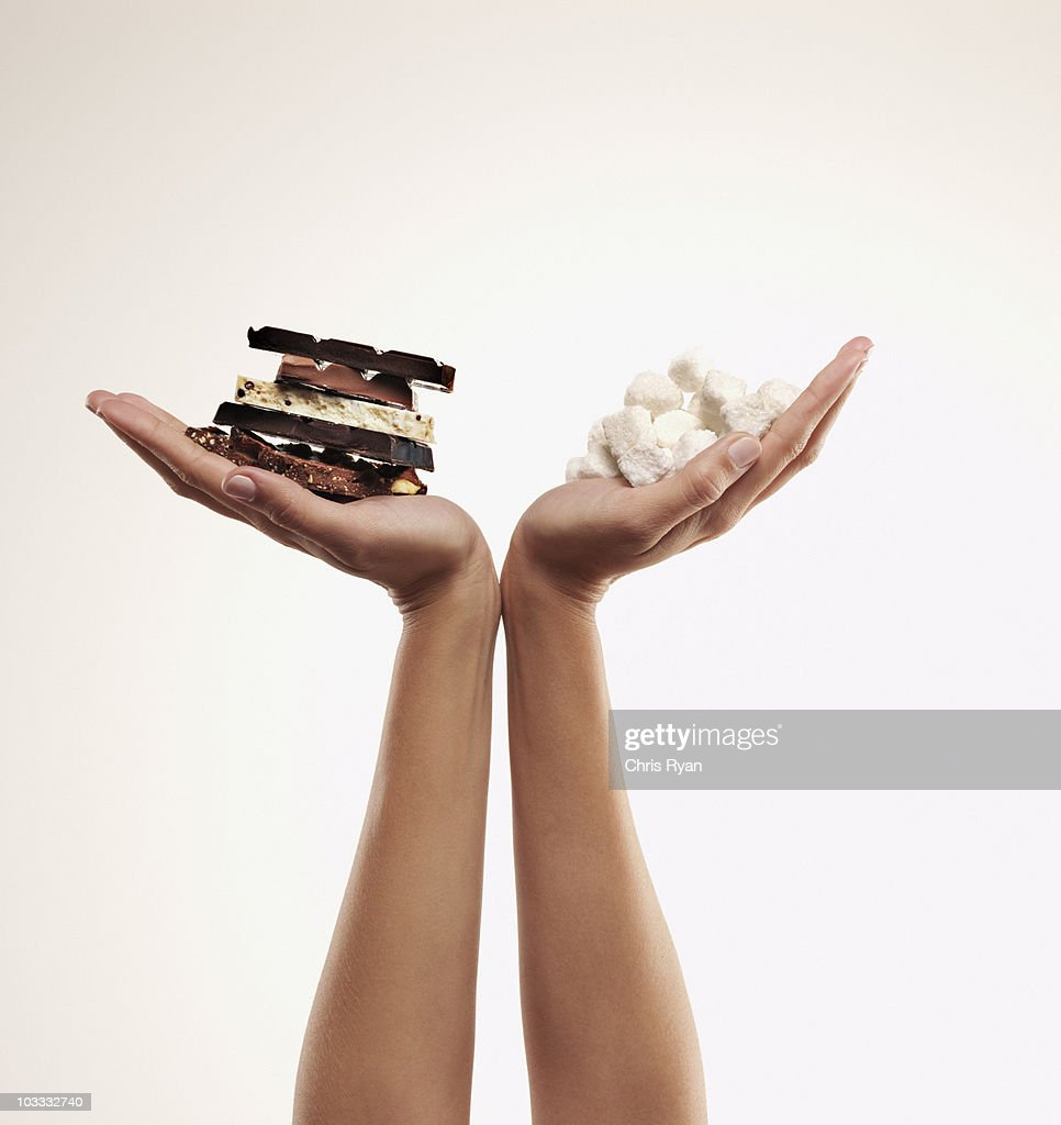 Hands cupping chocolate bars and sugar cubes : Stock Photo