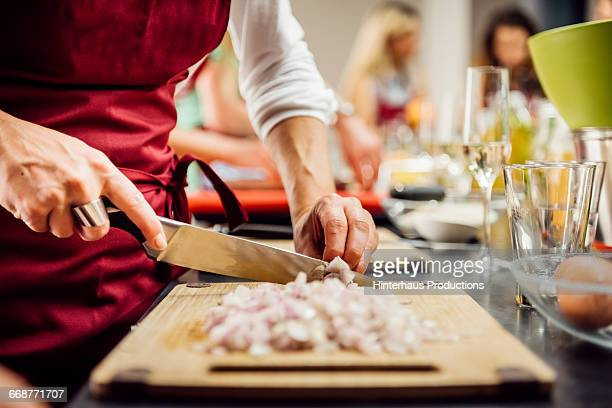 Hands cutting garlic