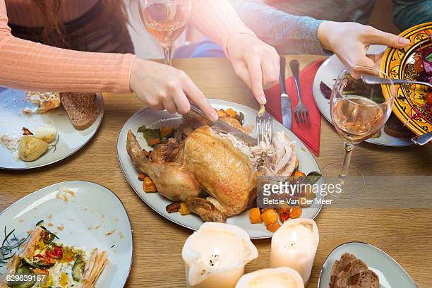 Hands cutting roast chicken at dinner table.