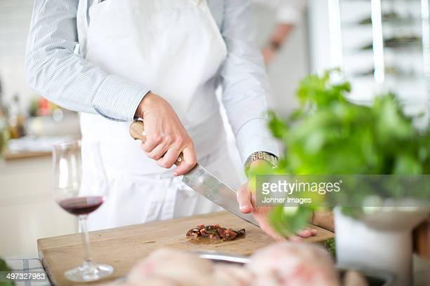 Hands cutting vegetable on cutting board