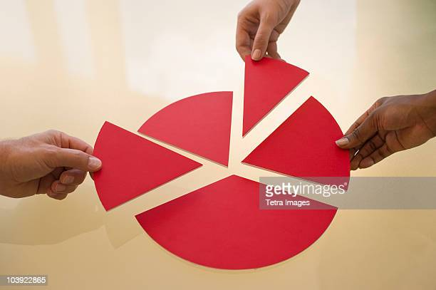 hands dividing pieces of pie chart - pie chart stock pictures, royalty-free photos & images