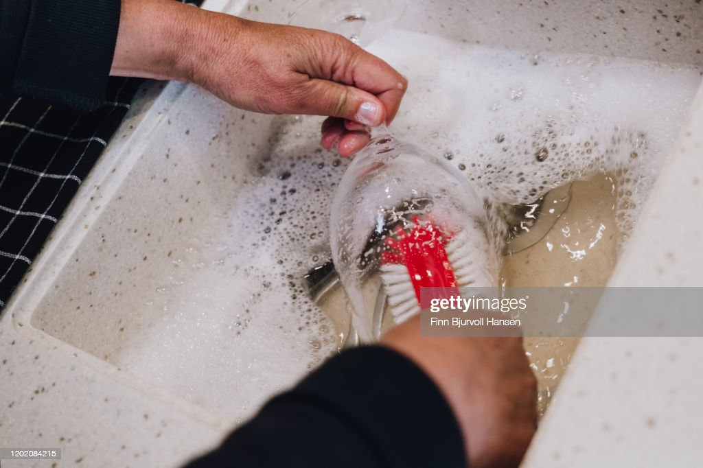 Hands doing manually dishing of a wineglass : Stock Photo