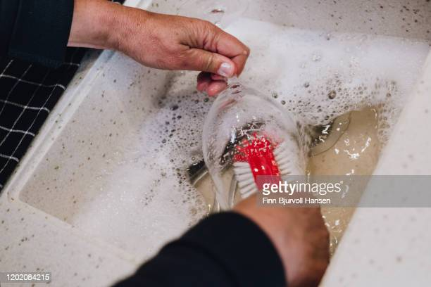 hands doing manually dishing of a wineglass - finn bjurvoll stock pictures, royalty-free photos & images