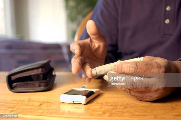 Hands drawing blood for glucose test