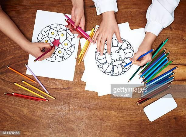 Hands drawing mandalas