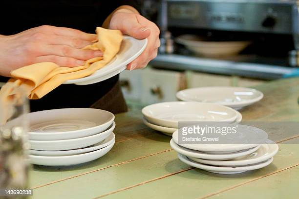 Hands drying dishes in kitchen
