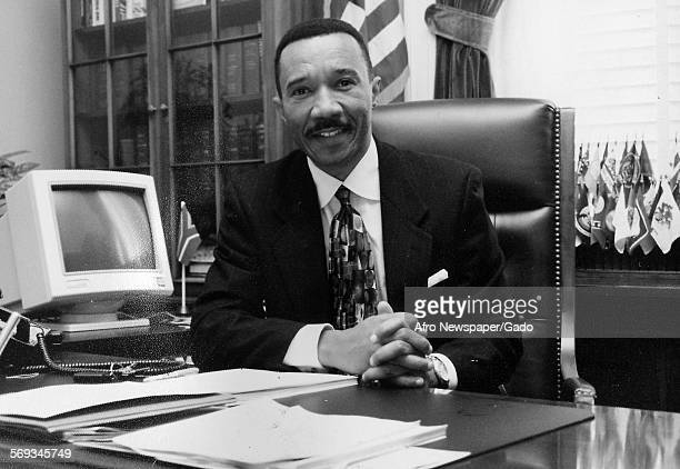 Hands folded on the table Kweisi Mfume sitting in an office Japan 1990 There is a computer monitor on the desk