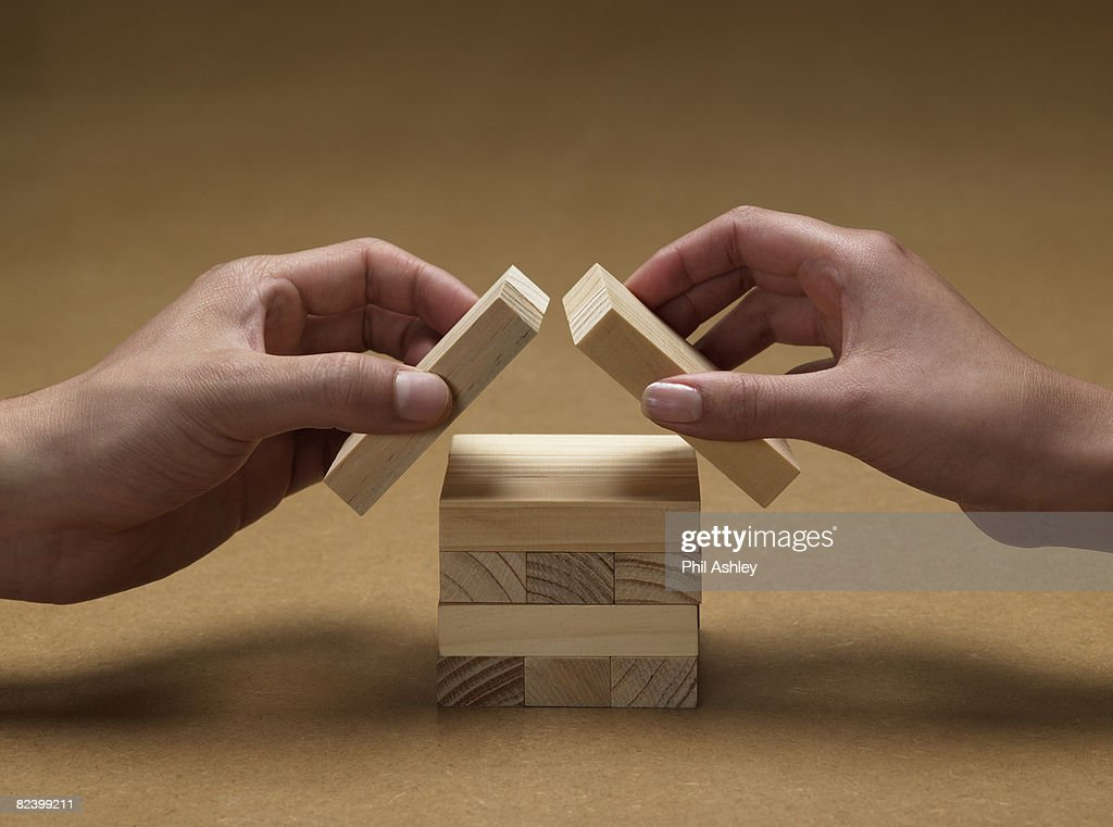 hands forming a house from wooden blocks : Stock-Foto